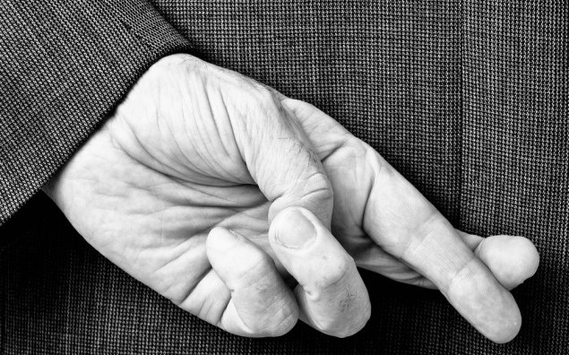 A B/W conceptial image of a business man with his fingers crossed behind his back.