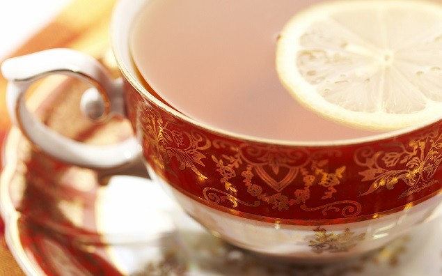 macro pic of a red cup of tea with lemon