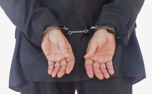 Rear view of businessman with handcuffs over white background