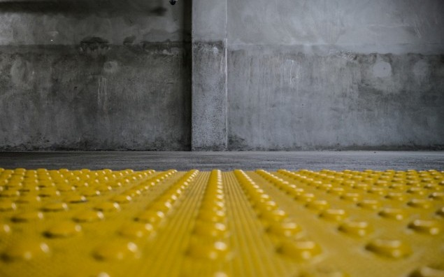 Grunge room interior with safety yellow bumps panel on floor. Copyspace.