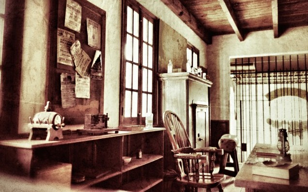 Vintage sheriff office. Desk with kerosene lamp and chair, strongbox on background. Filtered image