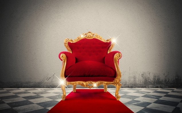 Sparkling golden armchair in a red carpet