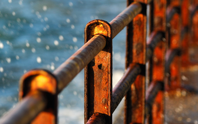Image shows a series of rusty protective barriers on a pier over splashing sea water. Image has shallow depth of field
