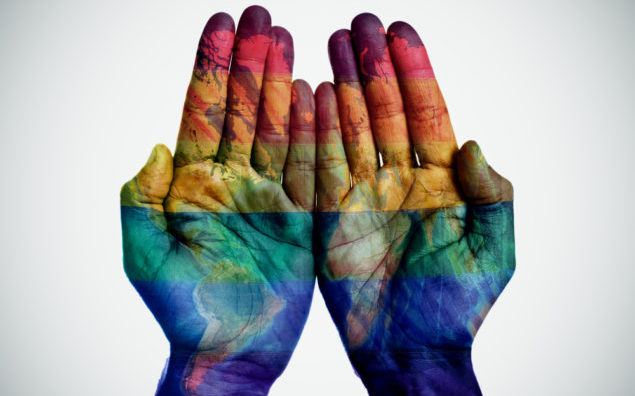 world map and rainbow flag in the hands