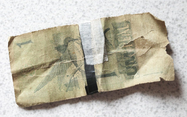Broken brazilian banknote with background. Real.