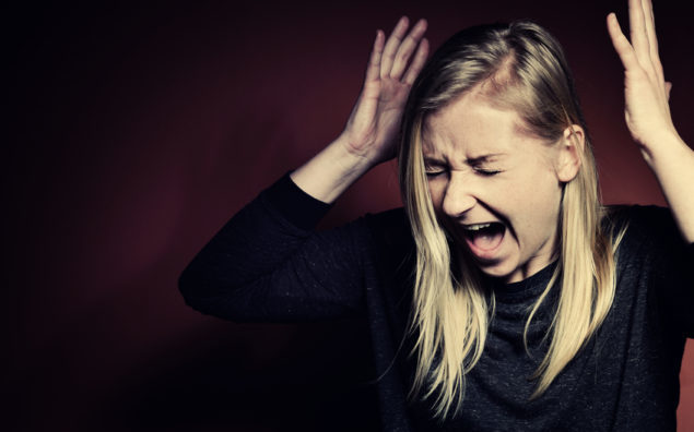 Blonde woman with hands in the air screaming in panic
