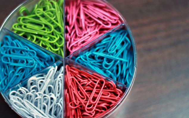 Brightly Colored Paper Clips Organized on Desk in Office