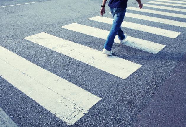 Man in jeans walking across a zebra crossing