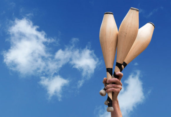 man's hand holding three juggling clubs in the blue sky